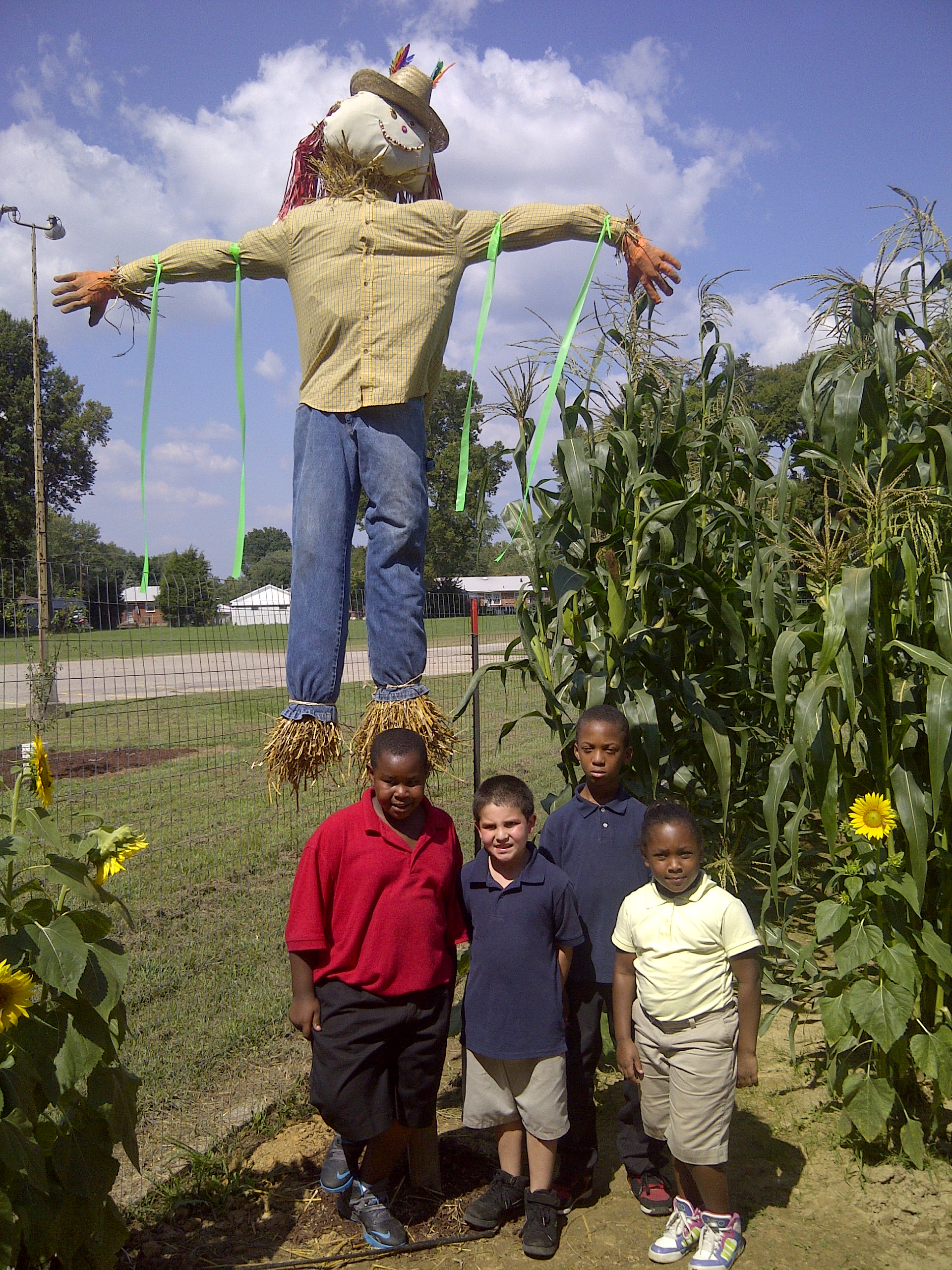 Students standing in front of their garden scarecrow.