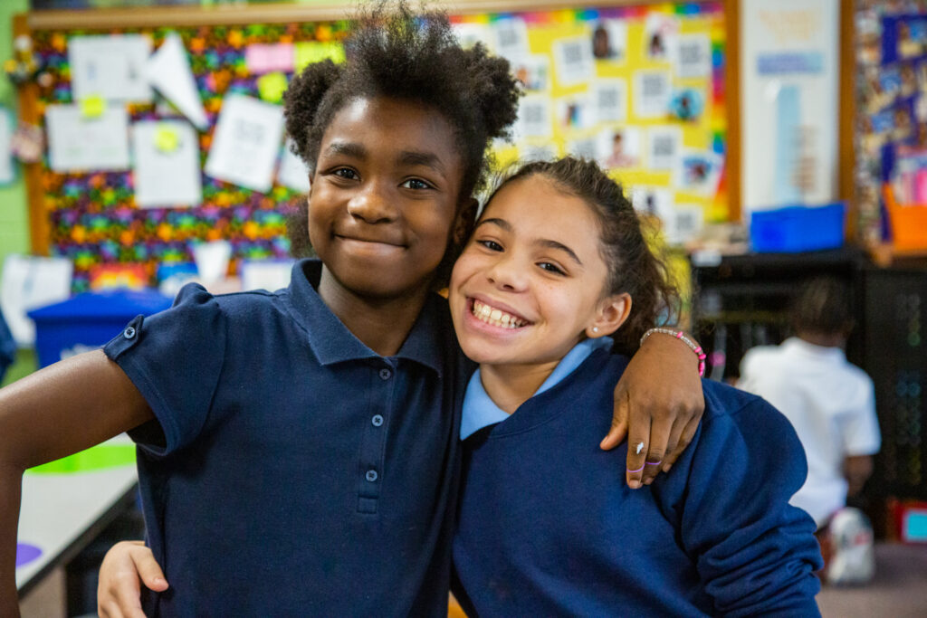 Two students smile for the camera.